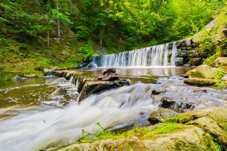 Beautiful small waterfall on nice creek in forest in Czech. Long exposure time, milky water effect, trees and green grass around, rocks and stones in water.