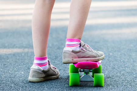 Young girl riding on skateboard on the road. Detail shot of legs, selective focus, smooth background.