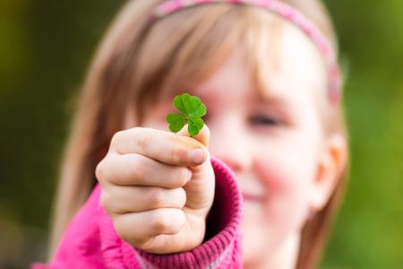 Trébol de cuatro hojas en la pequeña mano de la chica joven delante de su cara. Cara de niña en el fondo. Enfoque selectivo