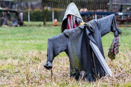Scarecrow on a farm. Old coat, old cloth.  Grass on a ground.