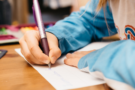 Child doing homework. A young girl writes on paper and uses a pen. Foto de archivo
