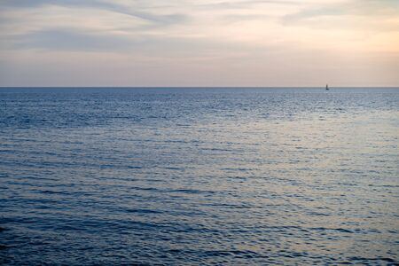 View of a small sailboat on the open sea horizon.