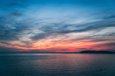 Sunset over the sea, colorful clouds, wide shot. Romantic picture full of colors. Reklamní fotografie