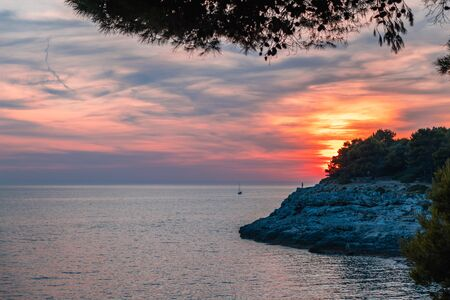 Sunset over the sea, colorful clouds, wide shot. Unrecognizable people on top of a rock. Romantic picture full of colors. Reklamní fotografie