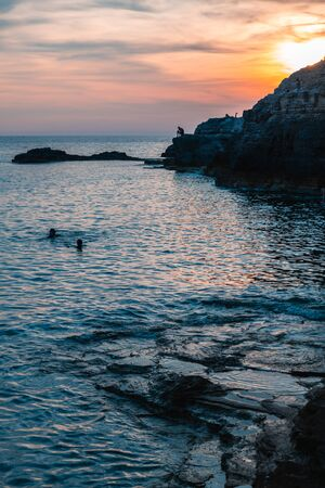 Silhouettes of unrecognizable people in the water and on the rocks by the sea. Reklamní fotografie