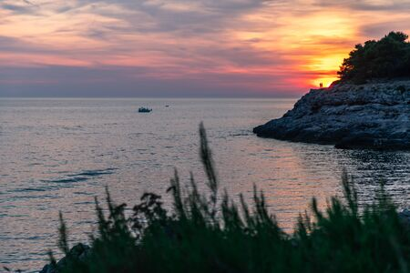 Sunset over the sea, colorful clouds, wide shot. Unrecognizable lovers on top of a rock.