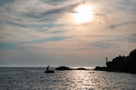 Silhouettes of unrecognizable people in the water and on the rocks by the sea. Sun is on the background.