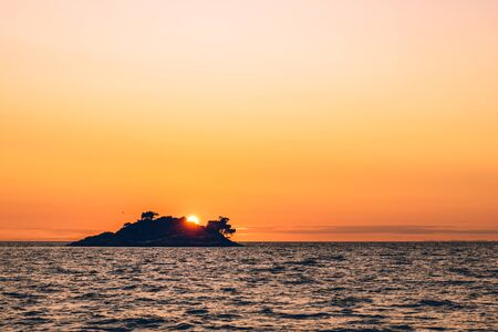 Romantic view of sunset over a deserted island in the distance at sea. View of the sea on the horizon.