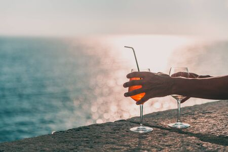 Hands holding two glasses with alcohol. In the background you can see the open sea and the horizon. Reklamní fotografie