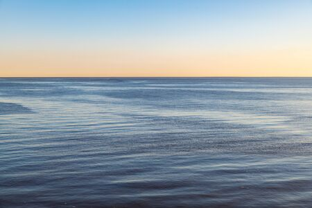 Distance view of empty sea with small waves. Morning, gold colors on the horizon.