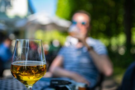Close up of glass with beer. An unrecognizable person is visible in the background. Reklamní fotografie