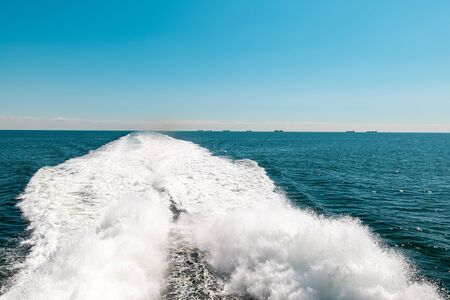 Sailing fast boat at sea, trail behind boat on water. Blue sky without clouds, clear horizon.