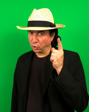 mafioso: Mafioso like man with light straw hat on a green background, lifting and pointing his finger and looking slightly angry,