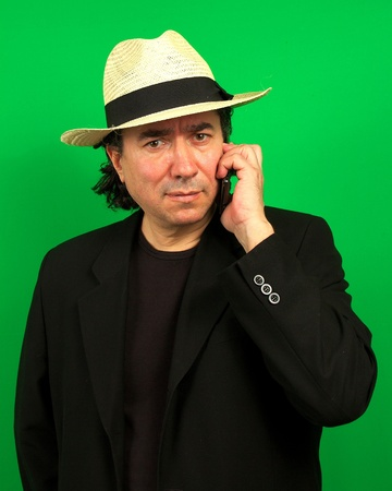 mafioso: Mafioso like latino talking in cell phone on a green screen background with dark hair  Stock Photo