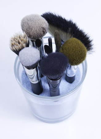 make up brushes: set of make up brushes in glass with blue sand