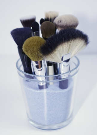 set of make up brushes in glass with blue sand