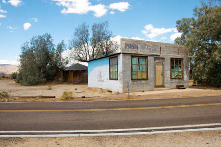 The old post building behind the road in small old town in the desert. Editorial