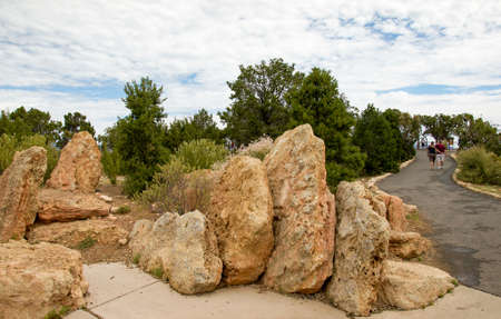 Sandstone rocks surrounded by trees with walk road with a loving couple walking on.
