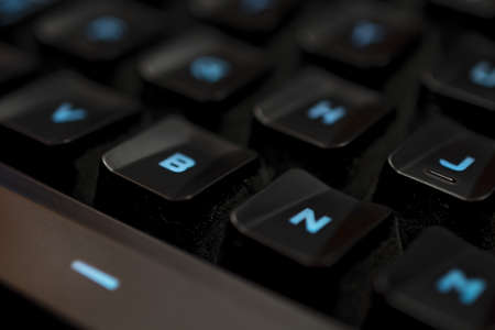 The mechanical backlighted keyboard black keycap with blue backlight detail. This image could be used as a theme of pc games. Stock Photo