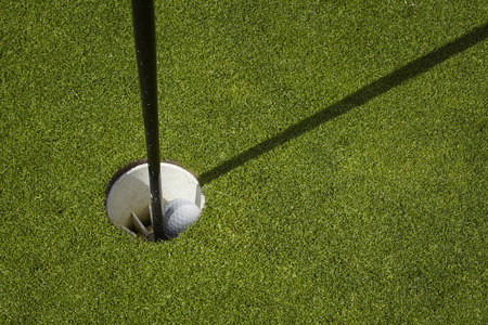 x marks the spot: Golfball sit inside cup on golf course putting green with flag.