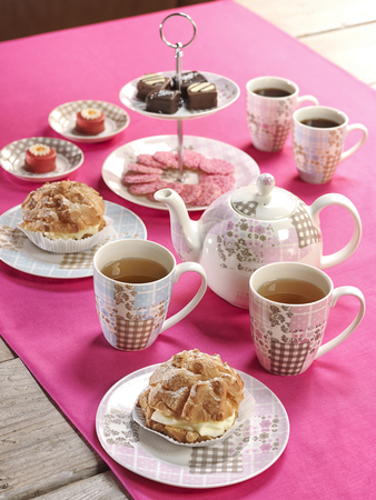 high tea on a table with a pink tablecloth
