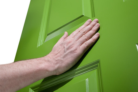 Man pushes a green door open with her hand Stock Photo