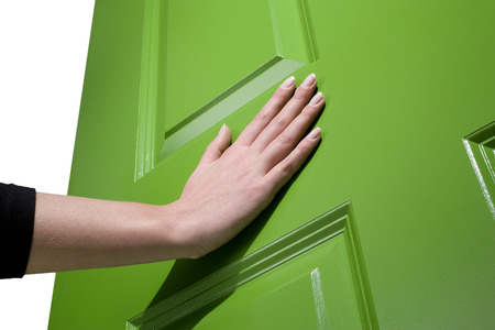 Woman pushes a green door open with her hand Stock Photo