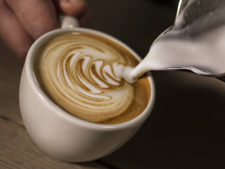 decaf: hand of barista making latte or cappuccino coffee pouring milk making latte art   Stock Photo