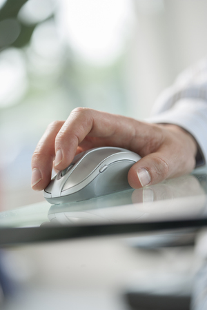 paypal: Image of a male hand clicking a cordless computer mouse on a green table Stock Photo