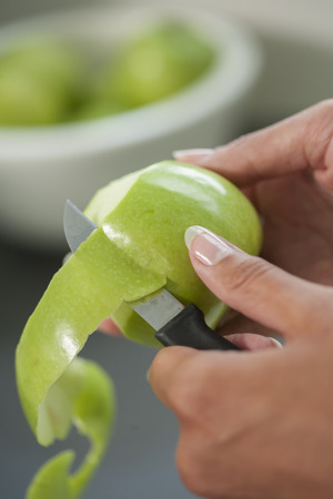paring: Close up of hand of a woman using a knife peeling an apple skin