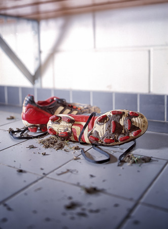 dirty football: Pair of dirty football shoes. Soccer boots in a dressing oom