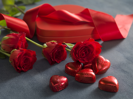 red hearts chocolates in front of red roses and hart shaped box. Valentines Day concept