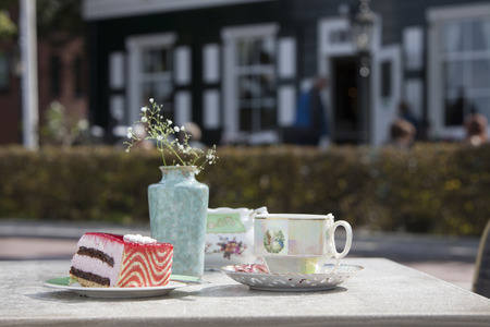 Table with strawberry chocolate cake and tea cup in courtyard Stock Photo