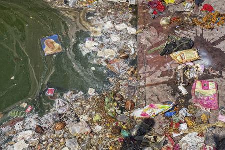 Contaminación en un río. Basura plástica, espuma, madera y desechos sucios en la orilla de un río