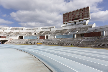 Old athletic stadium. Running healthy lifestyle concept. Blue sport track for running on stadium with tribune Stock fotó