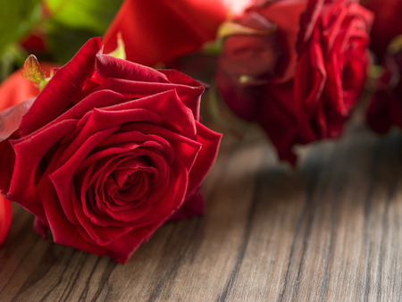 Funeral and mourning concept - red rose flower on wooden coffin. Close up