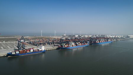 Aerial view of container terminal in the harbor MAASVLAKTE, Netherlands. A large containership from Cosco is unloading