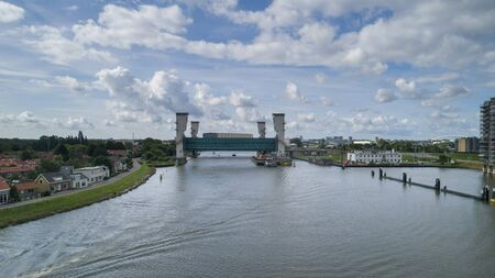the lifted Algera flood barrier in the river Hollandse IJssel in the background on a sunny day in summertime