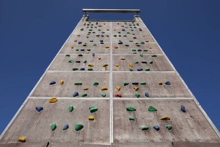 Background of empty climbing wall in a climbing center adventure park against blue sky