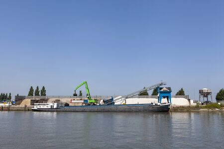 Loading barge with sand and rubble on a small berth. Freight transport logistics