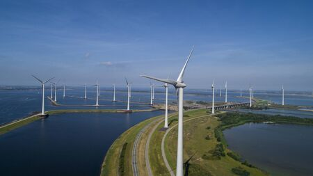 A Modern Wind Farm consisting of Wind Turbines with Two and Three Blades along the Shore of Grevelingenmeer under a Blue Sky in the Netherlands