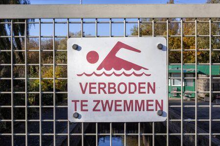 A no swimming danger sign at a lake