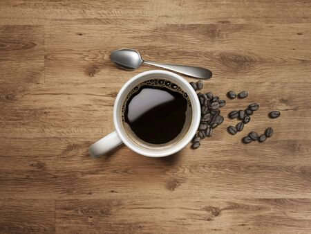 Coffee Mug with spoon and coffee bean on Wooden Table