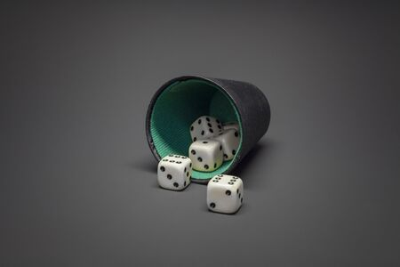 A black playing cup with several dices in the foreground