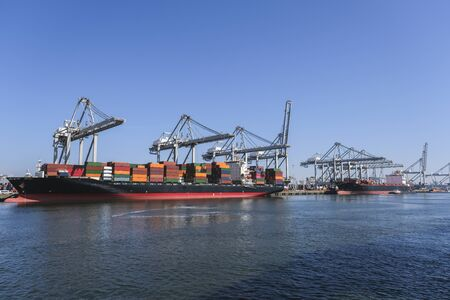 Huge cranes and ships anchored at harbor. International commercial port, city of Rotterdam background. Logistics business