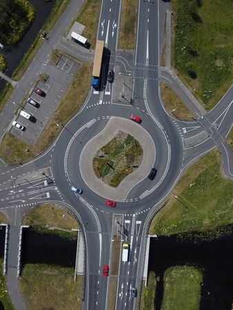 Aerial top down view of a traffic roundabout on a main road in an urban area of the Netherlands