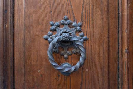 Antique door knocker on wooden door