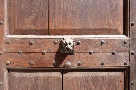 Antique door knocker on wooden door. Vintage, retro background