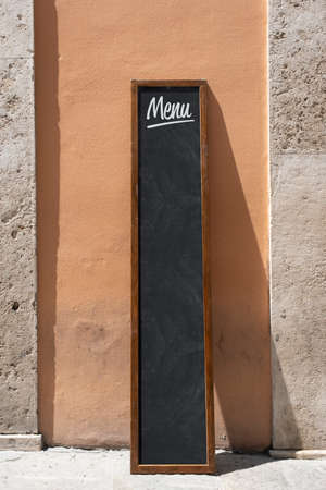Empty menu board stand and outdoor cafe in italy