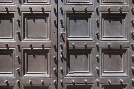 Metal spikes on old wooden door in italy